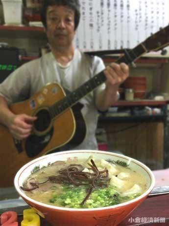 ギターで客をもてなす店主の田川さん